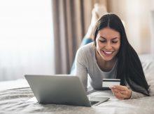 Kvinna med kreditkort vid dator